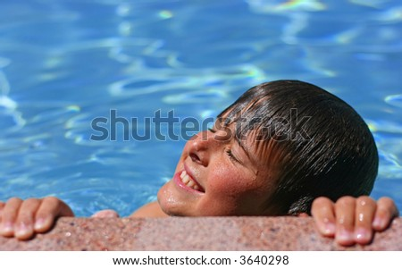 Young boy with eyes closed, smiling enjoying the sun in a swimming pool - stock photo