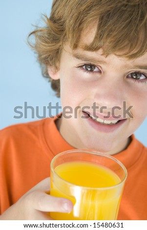 Young boy with glass of orange juice smiling - stock photo