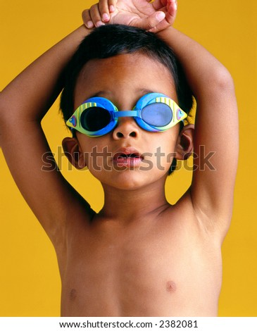 Young boy with goggles against yellow background