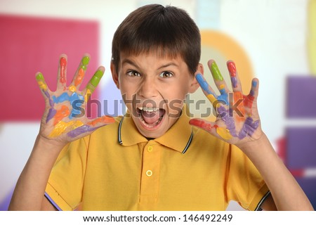 Young boy with hands painted expressing joy in art room