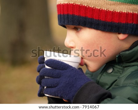 young boy with hat and gloves drinking hot chocolate outdoors - stock photo