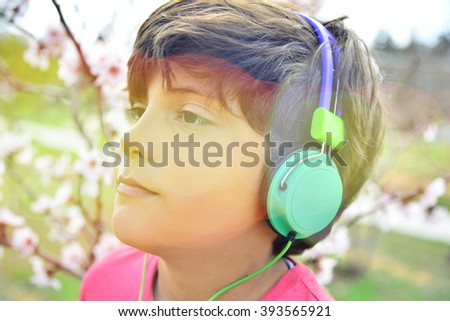Young boy with head phone set listening to internet tunes via smart phone