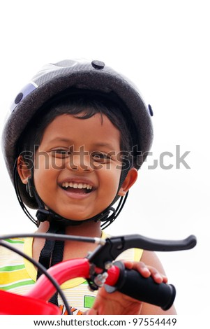 Young boy with helmet expressing happiness with a big smile as he rides a bike - stock photo