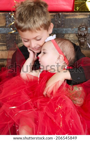 Young boy with his baby sister at christmas time - stock photo