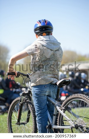 Young boy with his bicycle and bikers in city street - stock photo