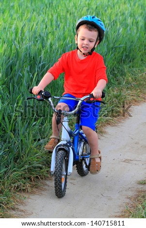 Young boy with his bike on the dirt road at sunset - stock photo