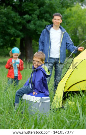 Young boy with his family near tent in camping on the nature - stock photo