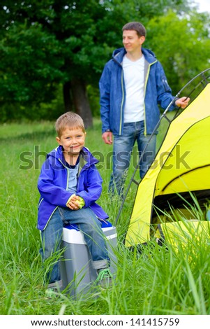 Young boy with his father near tent in camping on the nature - stock photo