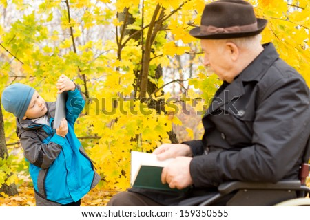 Young boy with his grandfather, who is sitting in a wheelchair, playing with his tablet computer watched over by the old man in an autumn forest - stock photo