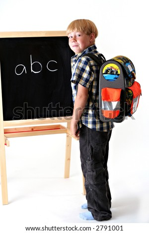 Young boy with his school backpack on next to a black board. Against a white background. - stock photo