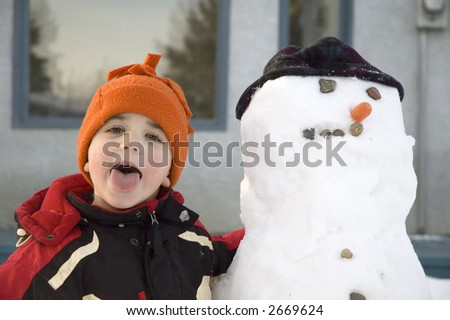 Young boy with his snowman.