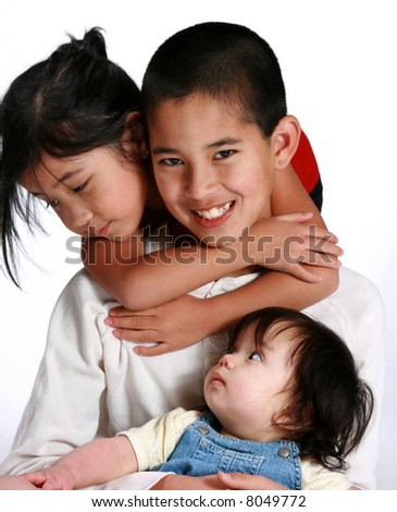 Young boy with his two younger sisters - stock photo