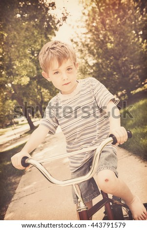 Young boy with injuries riding a bike - stock photo
