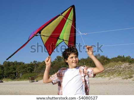 Young boy with kite outdoors smiling - stock photo