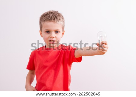 Young boy with light bulb - stock photo