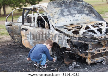 Young boy with luxury model car destroyed in a fire deliberately lit by vandals - stock photo