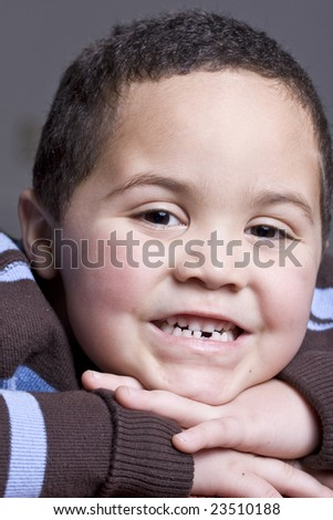 Young boy with missing baby tooth smiling