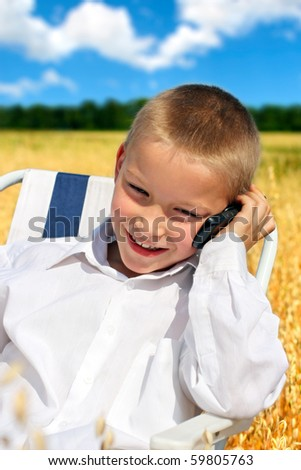 young boy with mobile phone outdoor - stock photo