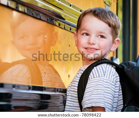 Young boy with nervous smile waits to board bus on first day of school. - stock photo