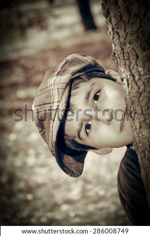 Young boy with newsboy cap sneaking behind a tree and playing detective. Vintage style photo  - stock photo