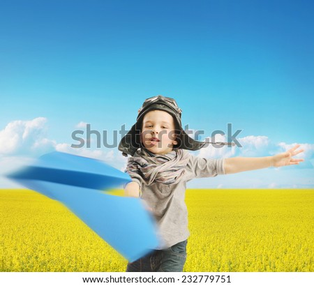 Young boy with paper airplane - stock photo