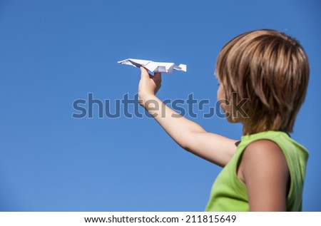 young boy with paper plane against blue sky - stock photo