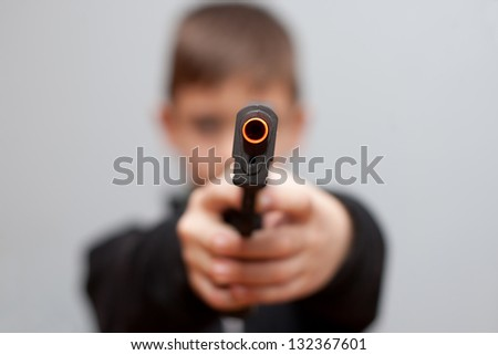 Young boy with plastic pistol - stock photo