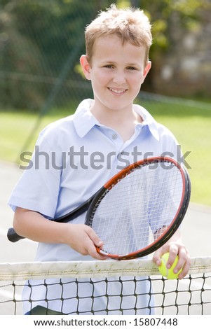 Young boy with racket on tennis court smiling - stock photo