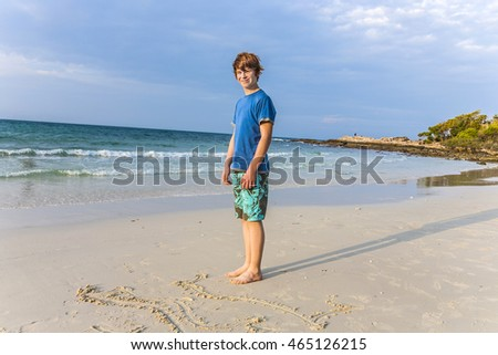 young boy with red hair  is writing a message in the sandy beach