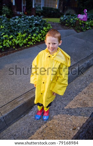 Young boy with red hair playing in the rain wearing yellow raincoat and rain boots