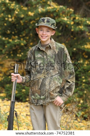 young boy with rifle in camouflage on first deer hunt - stock photo