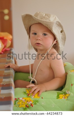 Young boy with safari hat sitting in chair