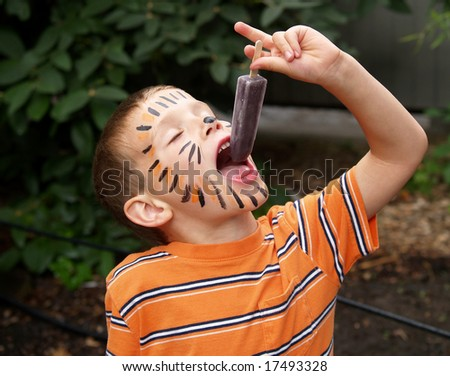 young boy with tiger face paint eating a frozen ice treat - stock photo