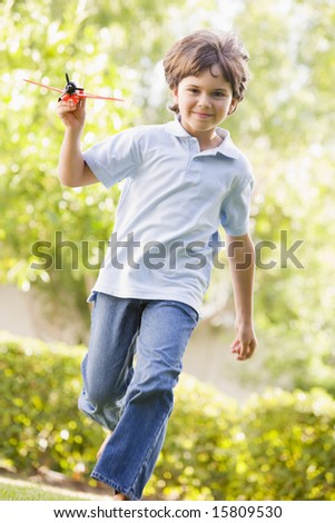 Young boy with toy airplane running outdoors smiling - stock photo
