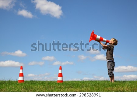 Young boy with traffic cones on a green meadow - stock photo
