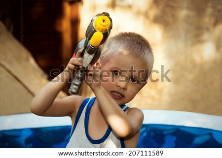 Young boy with water pistol in summer in the garden.