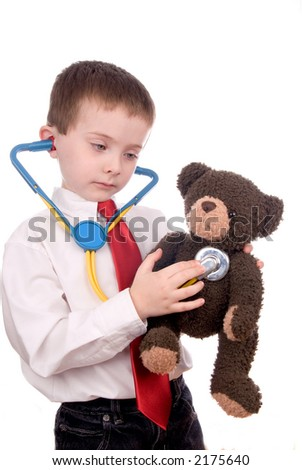 young boy with white shirt, stethescope and red tie giving a teddy bear a checkup - stock photo