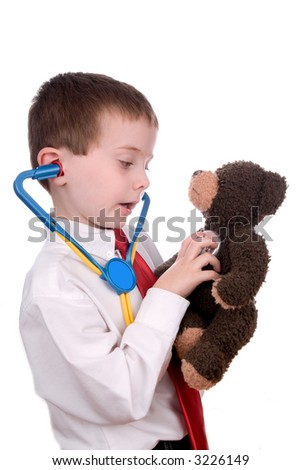 young boy with white shirt, stethoscope and red tie giving a teddy bear a checkup - stock photo