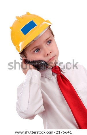 young boy with white shirt, yellow hardhat and red tie making a business business call - stock photo