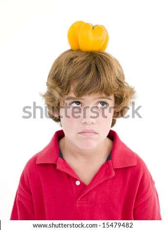 Young boy with yellow pepper on his head frowning - stock photo