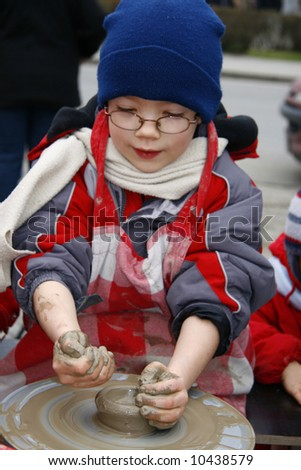 Young boy work with the ceramic wheel - stock photo