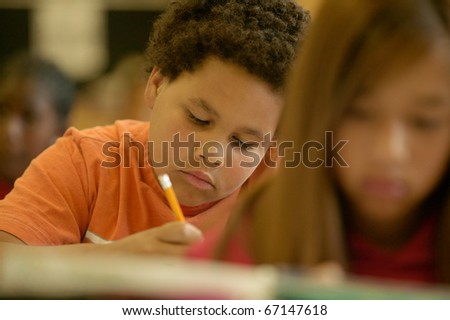 Young boy working in classroom - stock photo