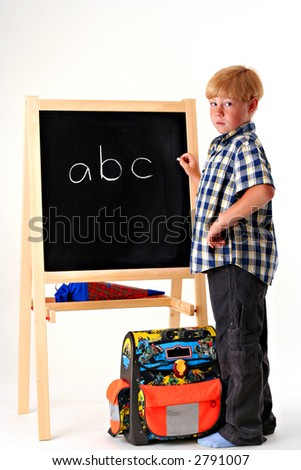 Young boy writing ABC in chalk on a blackboard on a white background - stock photo