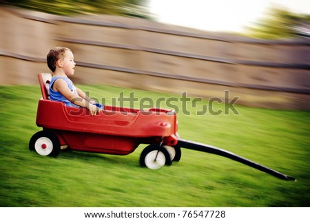 Young boy zooms downhill in wagon in image with motion blur. - stock photo