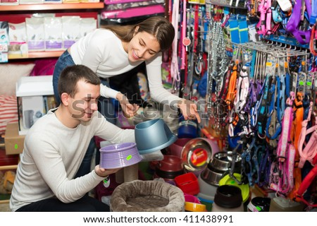 Young boyfriend helping girl to choose bowl in pet store. Focus on guy