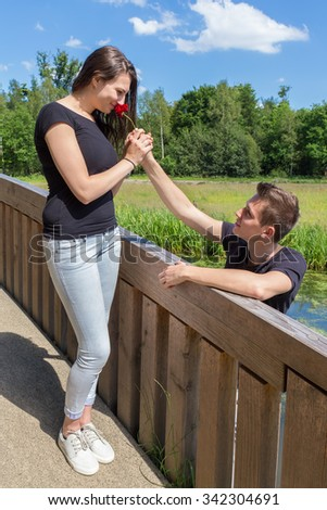 Young boyfriend offers red rose to attractive woman on bridge in nature - stock photo