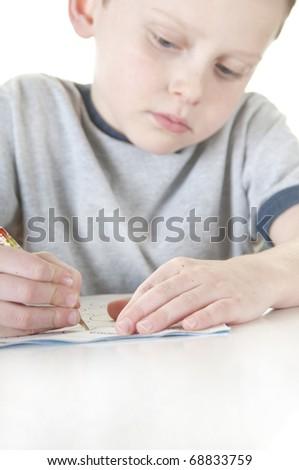 Young boyl doing homework...focus on pencil - stock photo