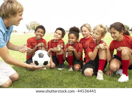 Young Boys And Girls In Football Team  With Coach - stock photo