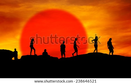 Young boys and girls silhouette walking on hill over red sunset - stock photo