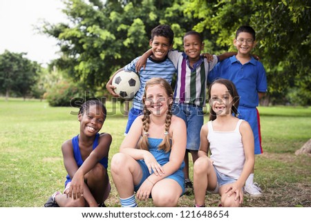 Young boys and sport, portrait of three young children with football looking at camera. Summer camp fun